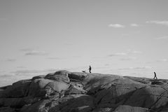 People and Dog walking on the Rocks. Two people walking to the top of the rocks with dog Royalty Free Stock Photo