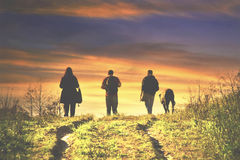 People and dog walking at sunset Royalty Free Stock Images