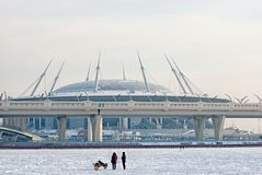 People and dogs near Zenit Arena Stadium. St.Petersburg. Russia. SAINT - PETERSBURG, RUSSIA - FEBRUARY 15, 2018: People with dogs on the ice of the frozen Gulf Royalty Free Stock Photo