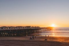 People doing activities at the beach near the pier with beautiful sunset. Pacific Beach in San Diego, California stock photo