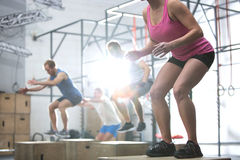 People doing box jump exercise in crossfit gym Stock Photo