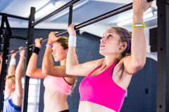 People doing chin-ups in gym Stock Photos