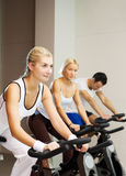 People doing exercise. Group of people doing exercise on a bike in a gym Royalty Free Stock Photos