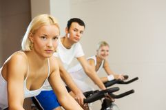 People doing exercise. Group of people doing exercise on a bike in a gym Stock Images