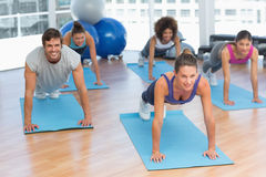 People doing push ups in fitness studio Stock Photos