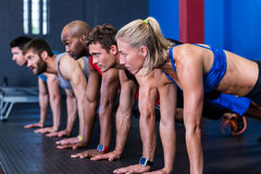 People doing push-ups in gym Stock Image