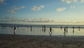People doing some activities during sunset time at Kuta Beach, Bali-Indonesia. Kuta beach is one place for hanging out all local and international tourist during stock image