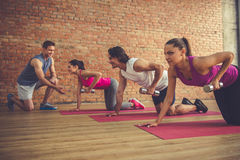 People doing sports. Beautiful sports people are doing exercises with dumbbells and smiling while working out with trainer in modern fitness hall Stock Photos