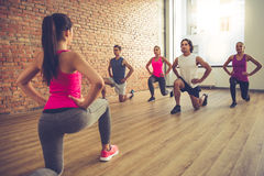 People doing sports. Beautiful sports people are doing exercises and smiling while working out with trainer in modern fitness hall Stock Photo