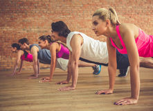 People doing sports. Beautiful sports people are doing plank and smiling while working out in modern fitness hall Stock Photography