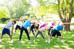 People doing stretching exercise in park Stock Photo