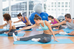 People doing stretching exercises in fitness studio Stock Photos