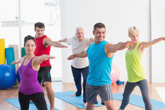 People doing warrior pose in yoga class. Fit men and women doing warrior pose in yoga class Royalty Free Stock Photo