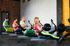 People is doing workout on the rowing machines stock photography