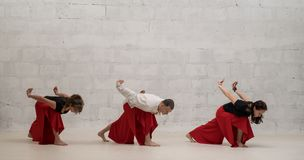 People Doing Yoga Exercises Shot Against Wall