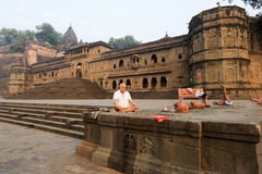 People doing yoga and meditation in front of Maheshwar palace Stock Photo