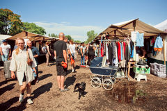People with domestic dogs spend time on the flea market. BERLIN, GERMANY - AUG 30, 2015: People with domestic dogs spend time on the flea market with vintage Royalty Free Stock Photography