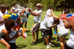 People Drench One Another In Group Water Gun Fight Stock Photo