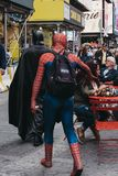 People dressed in Batman and Spiderman costumes walk through Tim. New York, USA - May 28, 2018: People dressed in Batman and Spiderman costumes walk through stock images