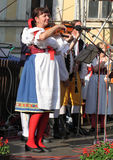 People dressed in Czech traditional garb dancing and singing. Stock Photos