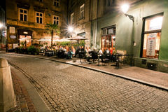 People drink outside the cafe in historical building Royalty Free Stock Image