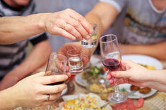 People drink at the table, clink glasses. Cheers Stock Photography