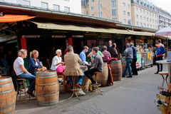 People drink wine and sit around the barrels. Near the small shop of market Naschmarkt  in Vienna, Austria. The popular Naschmarkt has existed since the 16th Stock Images