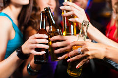 People drinking beer in bar or club. Group of party people - men and women - drinking beer in a pub or bar Royalty Free Stock Photo