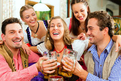 People drinking beer in Bavarian pub Stock Images