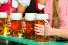 People drinking beer in Bavarian pub royalty free stock images