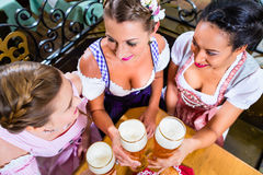 People drinking beer in Bavarian pub. People, tree women friends, drinking beer in Bavarian pub, top view royalty free stock photos