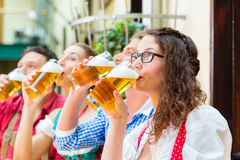 People drinking beer in Bavarian restaurant or pub Royalty Free Stock Images