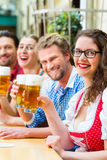People drinking beer in Bavarian restaurant or pub Stock Images
