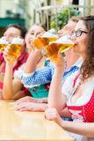 People drinking beer in Bavarian restaurant or pub Royalty Free Stock Image