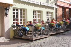 People are drinking beer and relax at a cafe terrace in the Old town of Vilnius, Lithuania Royalty Free Stock Images