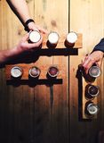 People drinking local beer from tasting palettes at craft brewery. A top-down view of a wooden table with three tasting palettes each containing three small Stock Images