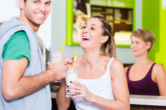 People drinking protein shakes in fitness gym Stock Photos