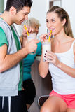 People drinking protein shakes in fitness gym Royalty Free Stock Photo