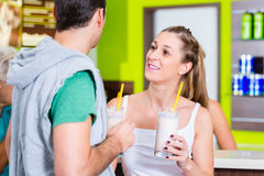 People drinking protein shakes in fitness studio Royalty Free Stock Image