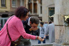 People drinking water from city fountain Stock Photography