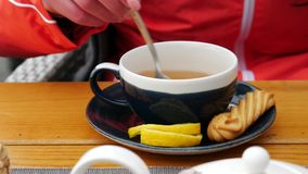 People and drinks concept - A woman`s hand stirs sugar in a cup of tea, closeup. People and drinks concept - Woman hands pouring sugar to the cup of tea stock video