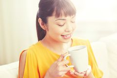 Happy asian woman drinking from tea cup. People, drinks and leisure concept - happy asian woman sitting on sofa and drinking tea from cup or mug at home Stock Photos