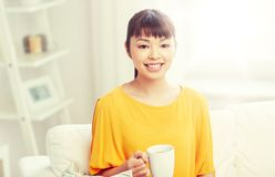 Happy asian woman drinking from tea cup. People, drinks and leisure concept - happy asian woman sitting on sofa and drinking tea from cup or mug at home Stock Image