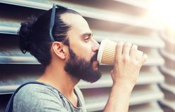 Man drinking coffee from paper cup on street. People, drinks, leisure and lifestyle - man drinking coffee from disposable paper cup on city street Stock Images