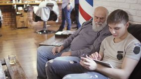 People drinks whiskey and waits their turn in barbershop playing in videogame. Mature man with young guy sits on sofa in a hall of barbershop and uses tablet stock footage