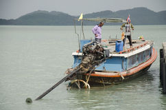 People drive wooden ship and mooring at Koh Yao Noi Harbor for s Stock Photo