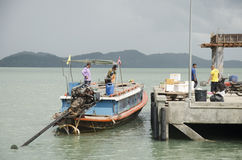 People drive wooden ship and mooring at Koh Yao Noi Harbor for s Stock Photos