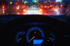 People driving modern car in night time with light and drop of water bokeh. At raining day Stock Image