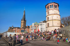 People in Dusseldorf. DUSSELDORF, GERMANY - MARCH 20, 2014: Crowd of people sitting at the steps in front of Schlossturm in Altstadt in the sunny spring day Royalty Free Stock Images