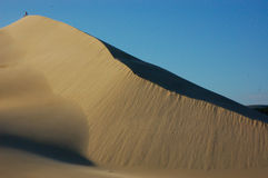 People dwarfed by high sand dune Stock Images